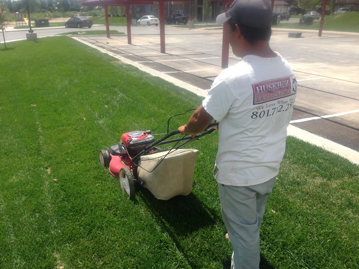 Huskie'z Landscaping employee working on mowing a lawn