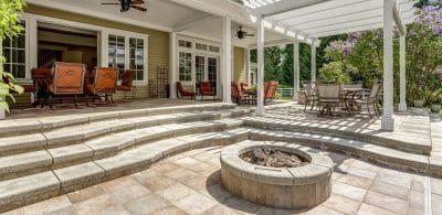 Lovely outdoor deck patio space with white pergola, fire pit in the backyard of a luxury house