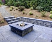 rectangular concrete fire pit framed by slate pavers and overlooking the lush garden