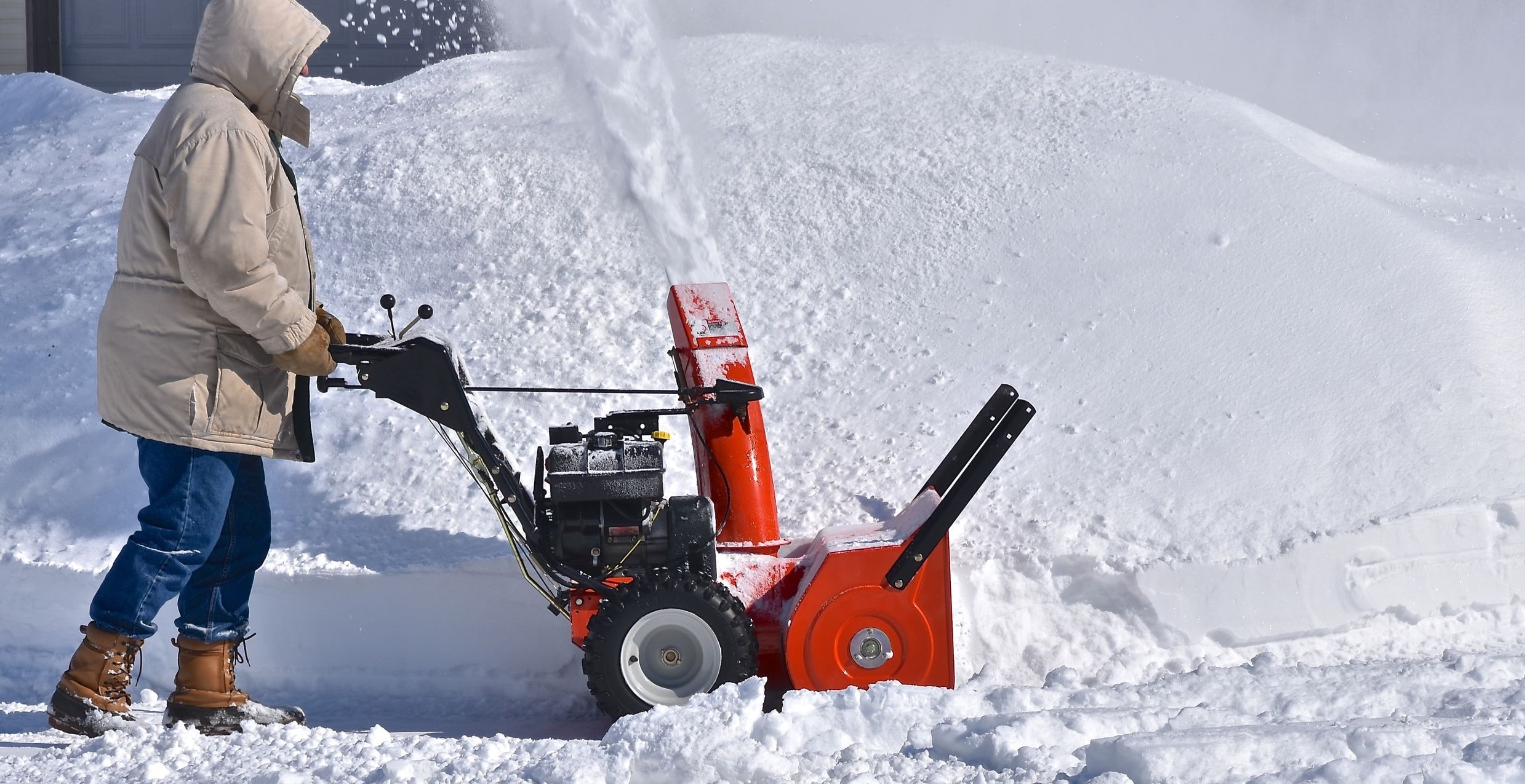 Man clearing sidewalk with snow blower