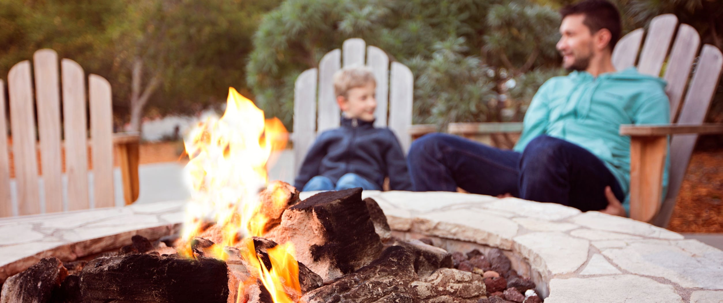 Man and son sitting by outdoor firepit
